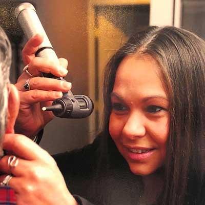 Jennifer Burget, Hearing Instrument Specialist, examining a client's ear.