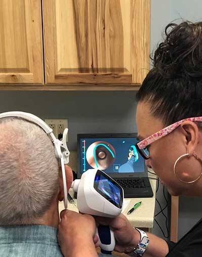 Jennifer Burget, Board Certified Hearing Instrument Specialist performing tests on a client
